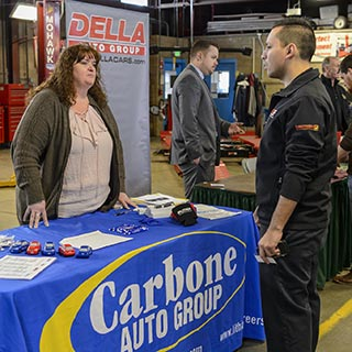 Student talking to a car dealership employee at a job fair