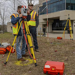 Students using surveying equipment to survey land on campus