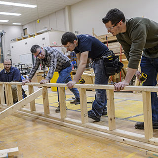 Construction students framing wood for a project