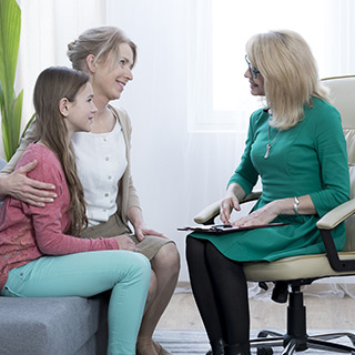 Counselor meeting with a mother and daughter in an office