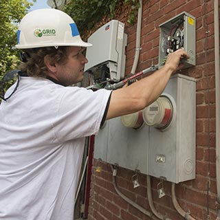 Electrician working on a power box at a home