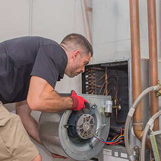 Individual working on installing a heating, ventilation and air conditioning unit