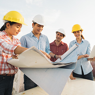 Individuals reading blueprints at a construction site
