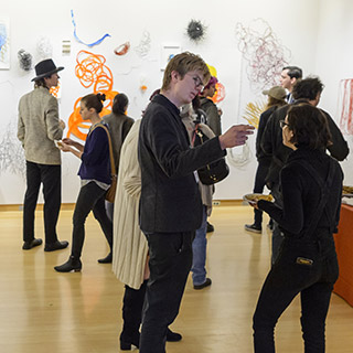 Individuals at an art reception in the Teaching Gallery on campus