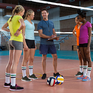 Volleyball coach talking to his players