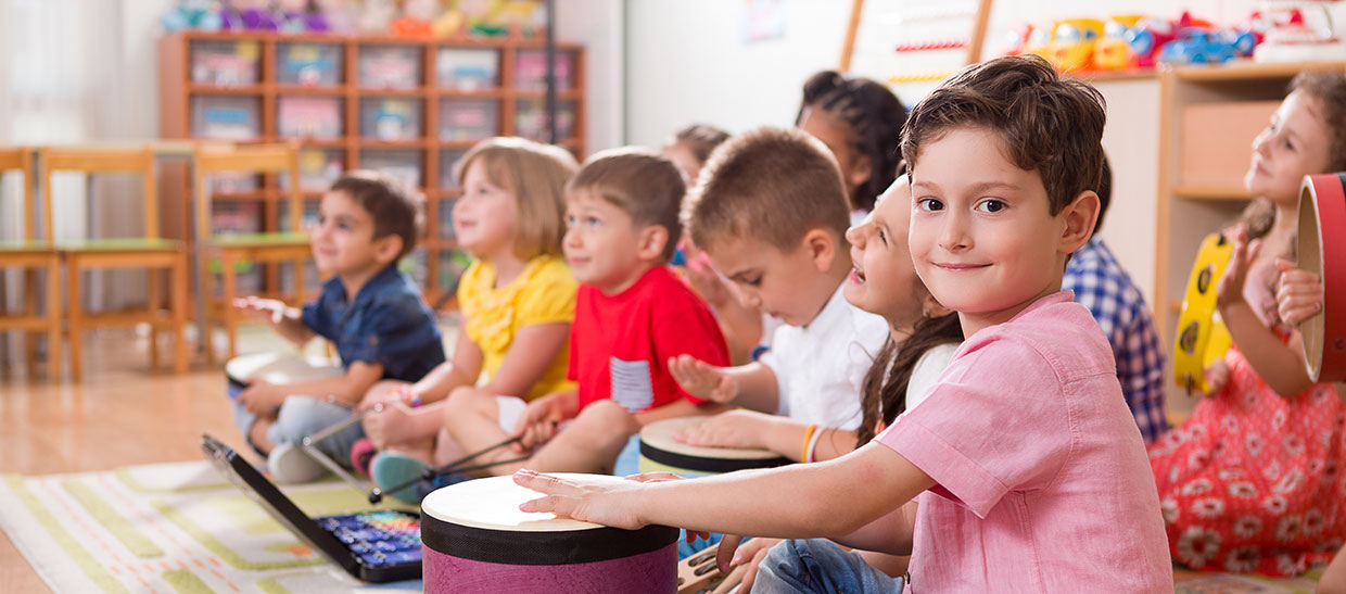 Group of children playing drums and other music instruments
