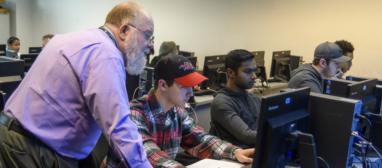Students working with a professor at a computer