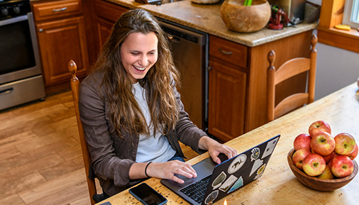 Student sitting at kitchen table doing school work on laptop