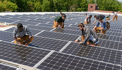 Multiple students working on solar panels on a roof